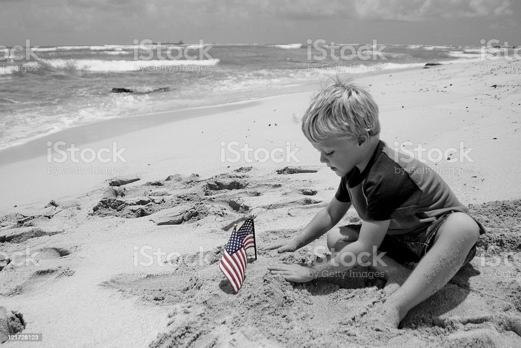 Boy with American Flags on a Beach stock photo