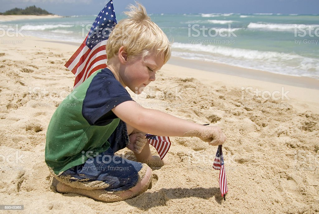 Boy with American Flags on a Beach royalty-free stock photo
