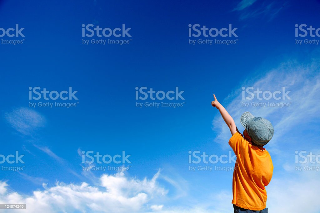 A boy with an orange shirt pointing at the sky royalty-free stock photo