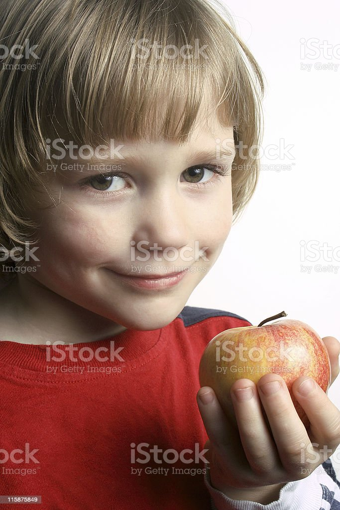 Boy with apple, smiling, against a white background stock photo