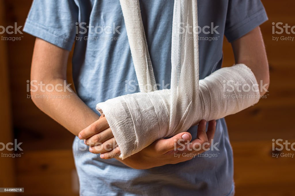 Boy with arm in plaster indoors on the brown background stock photo