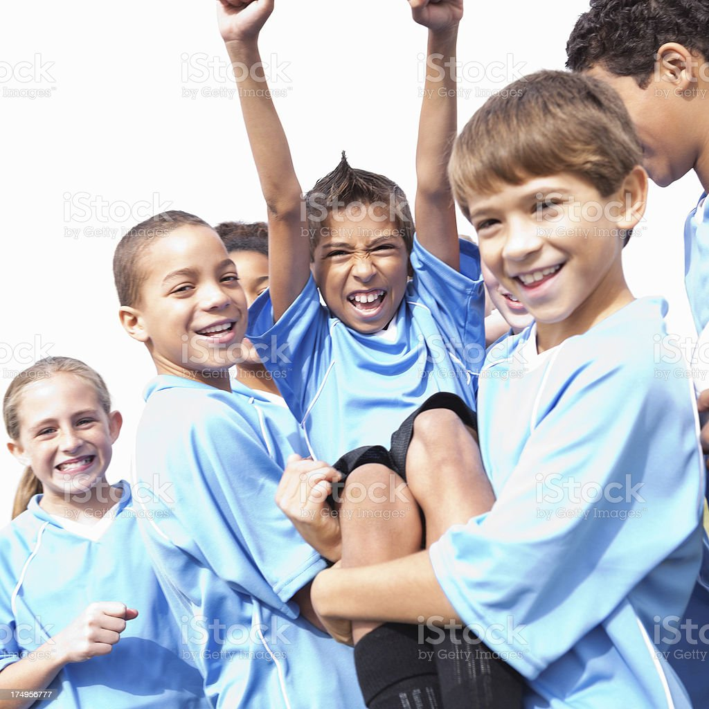 Boy with arms raised high carried by his teammates royalty-free stock photo