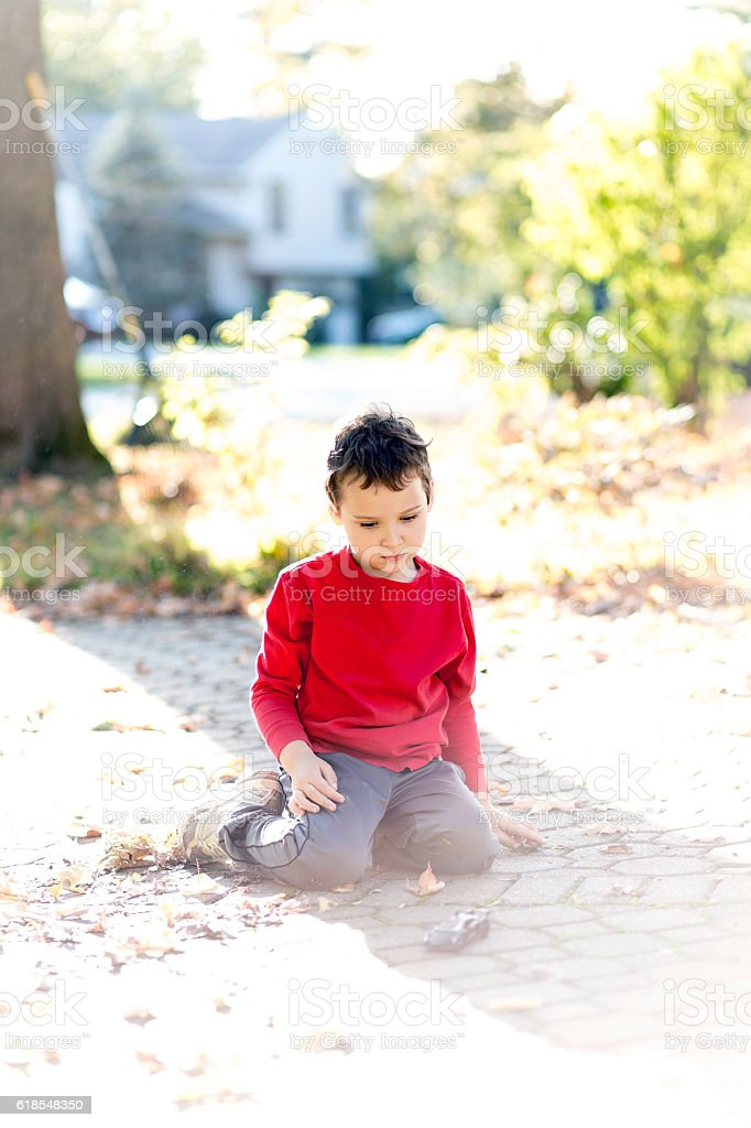 Boy with autism playing quietly outside with his toy car stock photo
