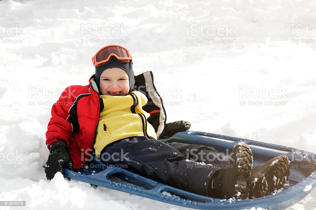 Boy with autsim on a sled playing in the snow stock photo
