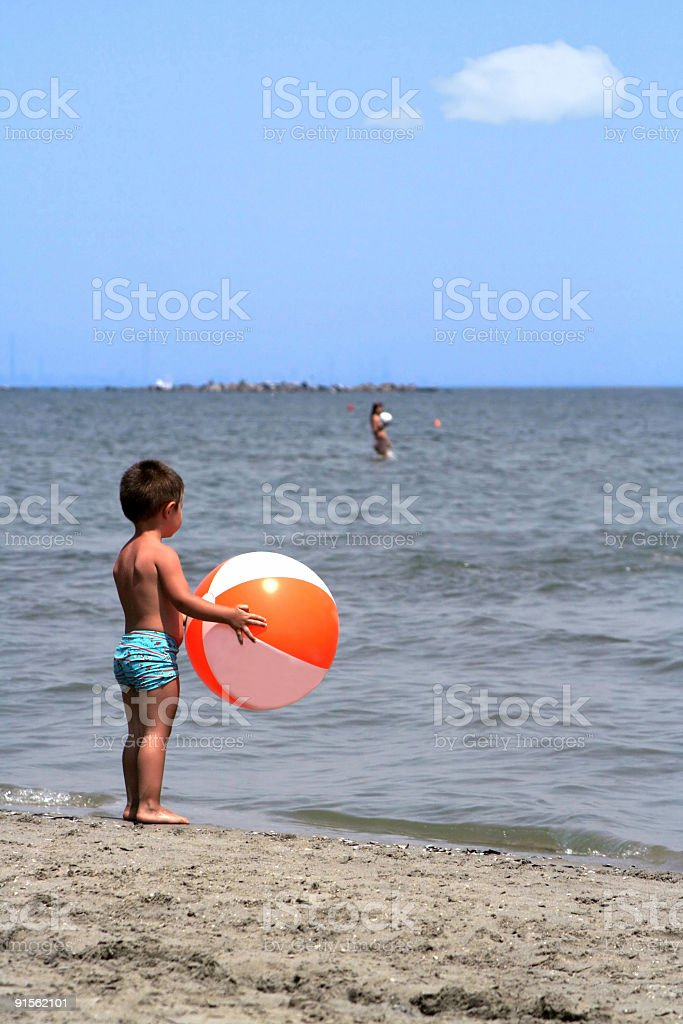 Boy with ball on the beach stock photo