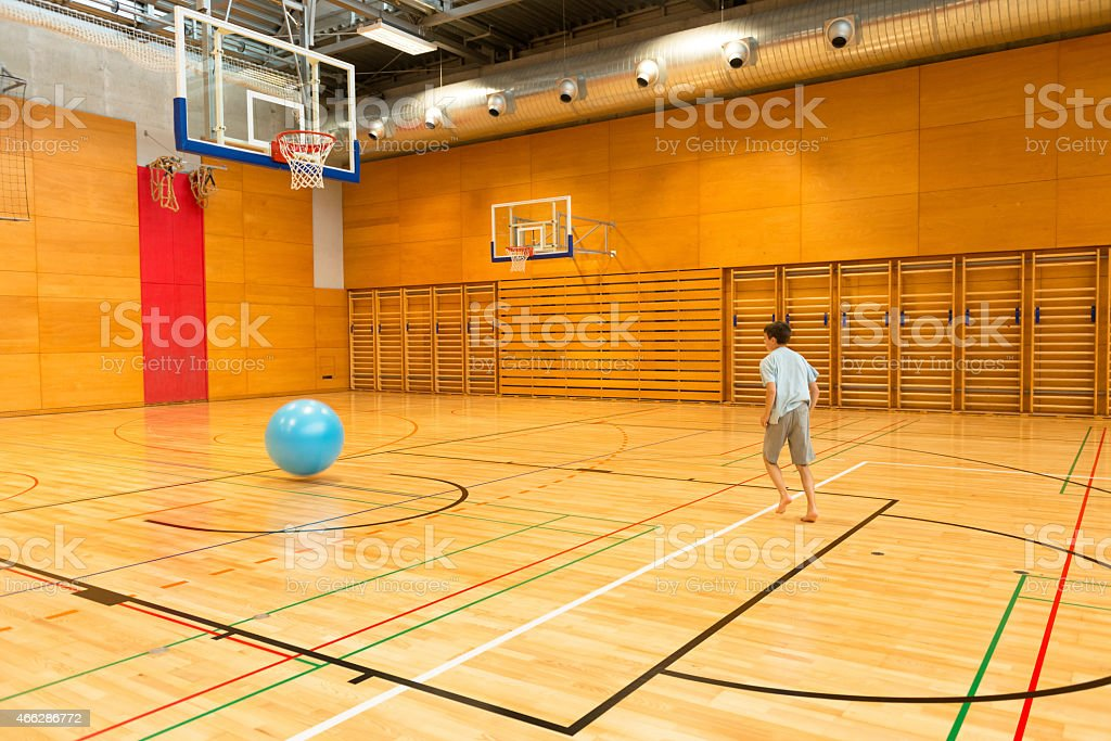 Boy with Big Blue Fitness Ball Playing Baskertball, School Gymnasium stock photo