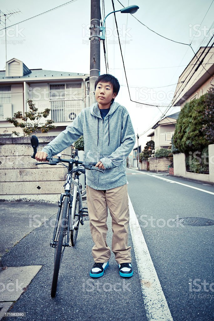 boy with bike in the street royalty-free stock photo