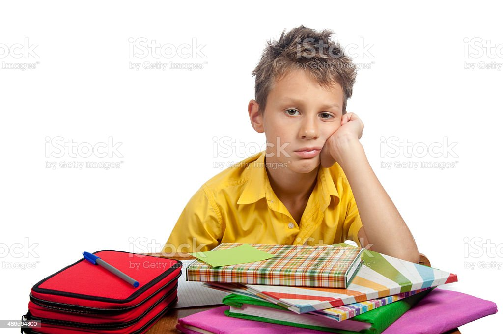 Boy with books looking bored. All on white background. stock photo