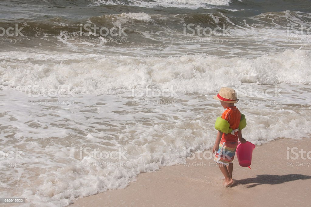 Boy with Bucket at Water's Edge stock photo