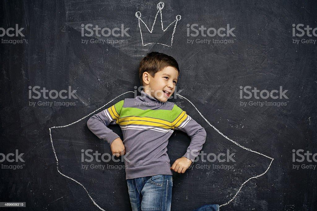Boy with chalk crown and cloak drawn around him stock photo
