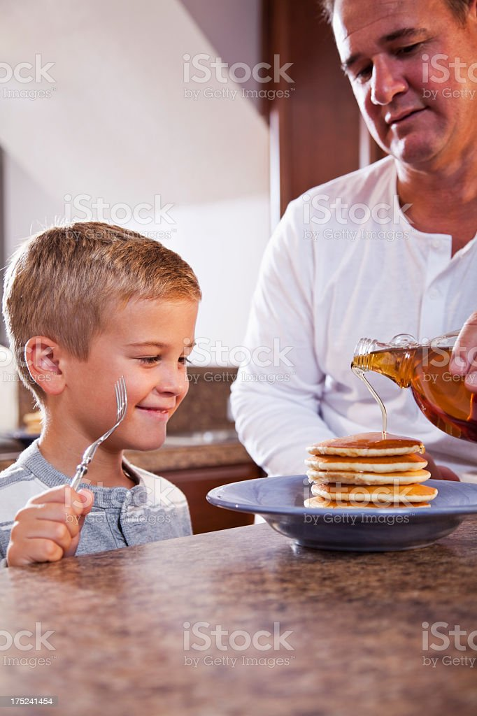 Boy with dad having pancakes for breakfast stock photo