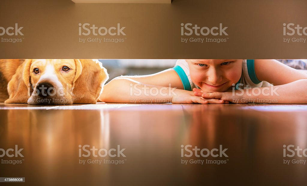 Boy With Doggy Friend Looks Under The Bed stock photo