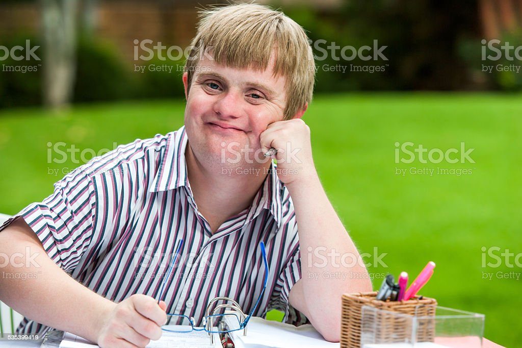 Boy with down syndrome at desk holding glasses. stock photo