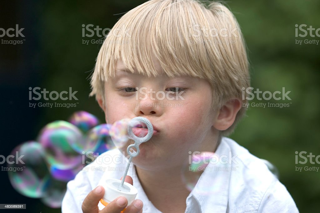 Boy with Down Syndrome blows bubbles stock photo