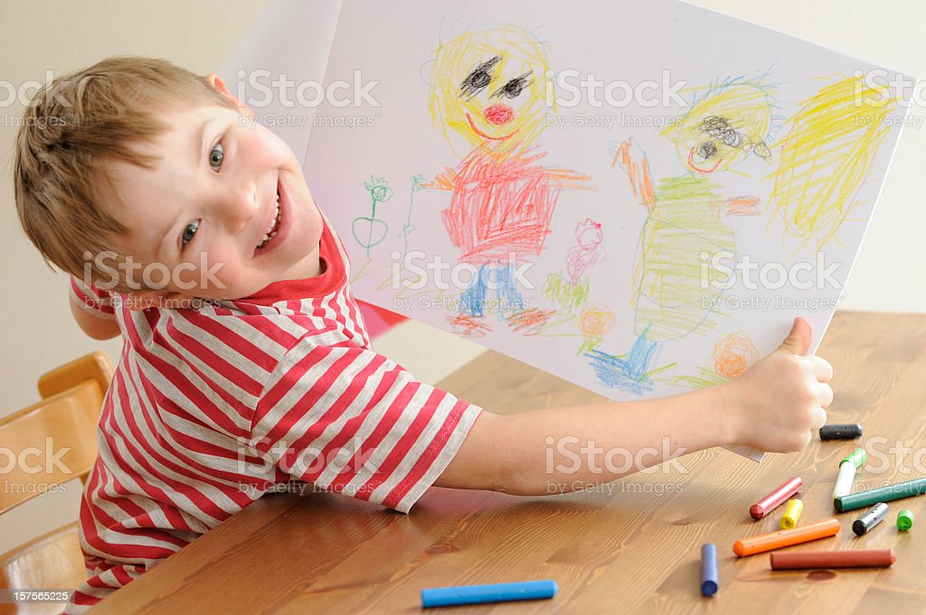 Boy with Down Syndrome shows his drawing stock photo