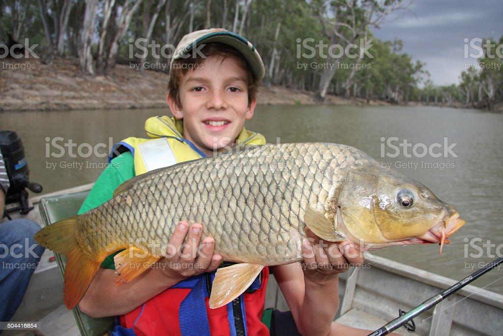 Boy with European carp stock photo