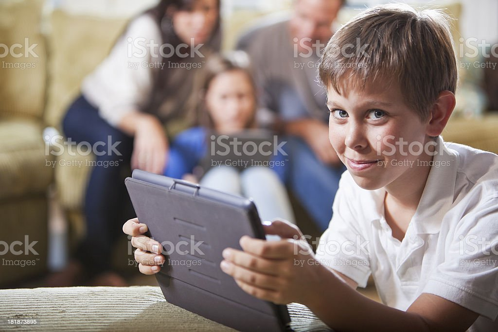 Boy with family using digital tablets stock photo