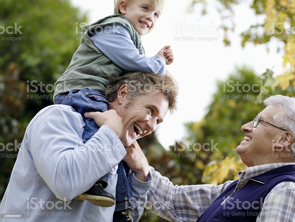 Boy With Father And Grandfather Enjoying In Park stock photo