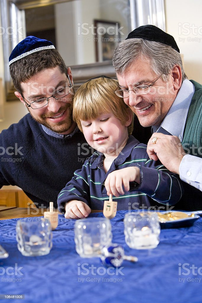Boy with father and grandfather spinning dreidel stock photo