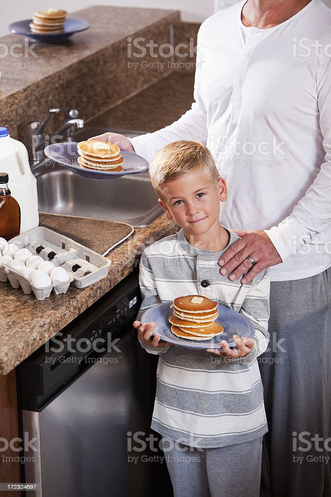 Boy with father having pancakes for breakfast stock photo