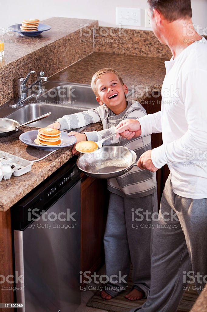 Boy with father making breakfast stock photo