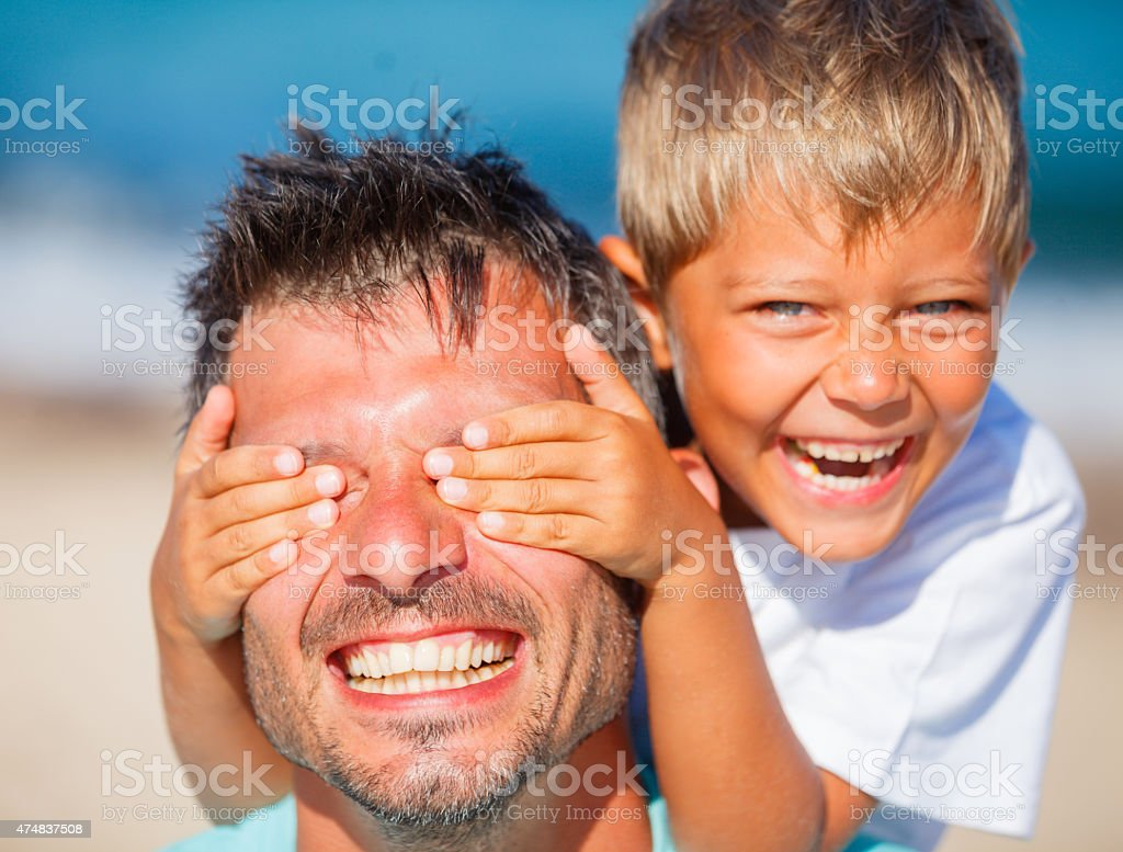 boy with father playing at the beach stock photo