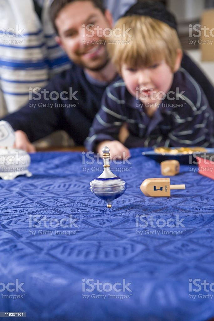 Boy with father spinning dreidel stock photo