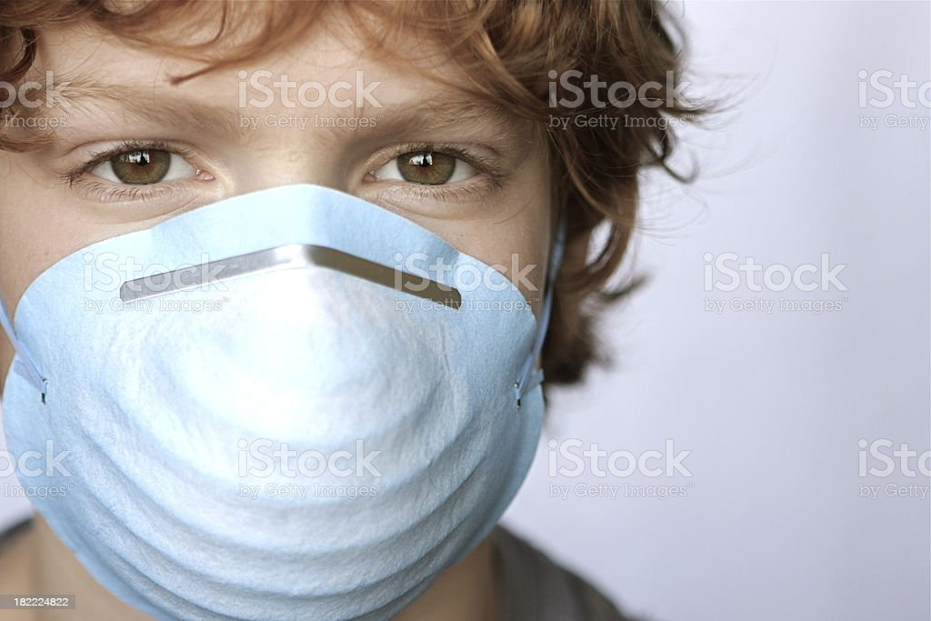 A close up portrait of a young boy with the flu virus wearing a mask....
