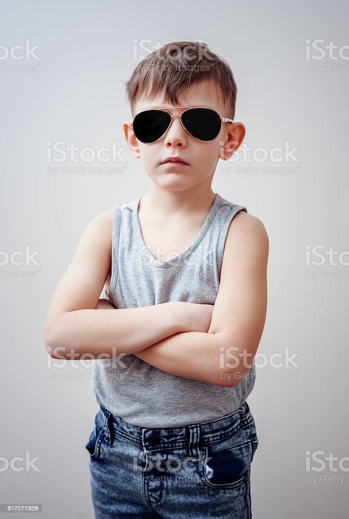 Boy with folded arms and sunglasses stock photo