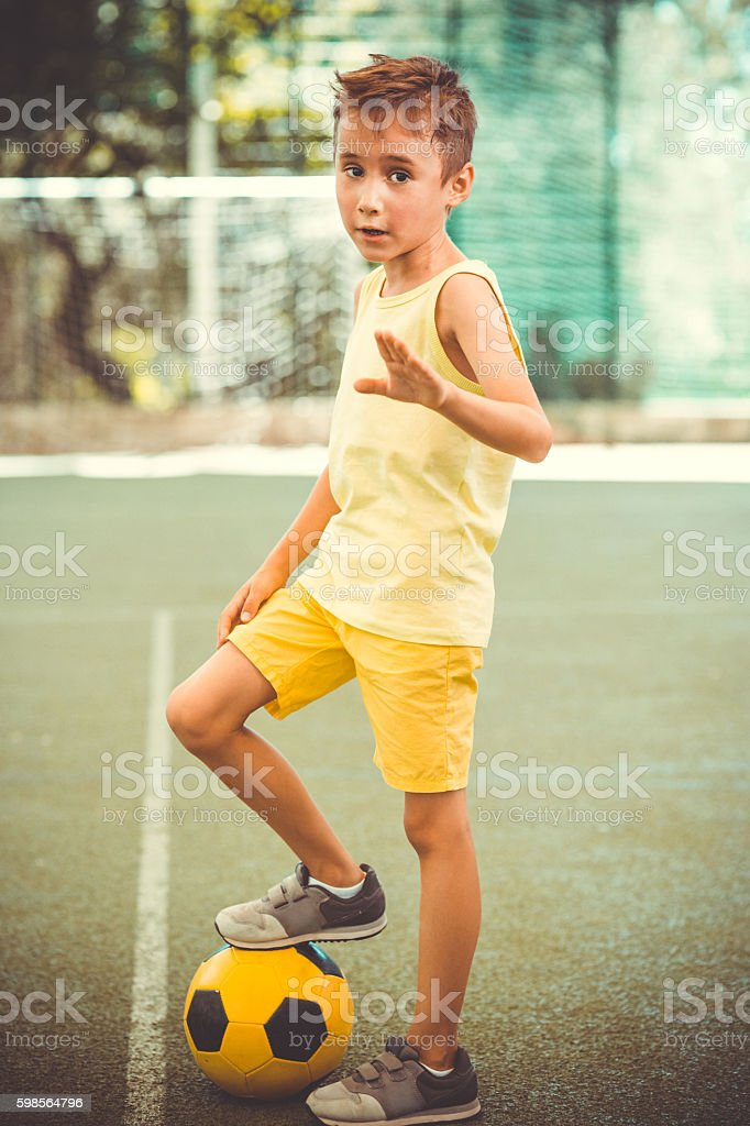 Boy with  football ball on stadium stock photo