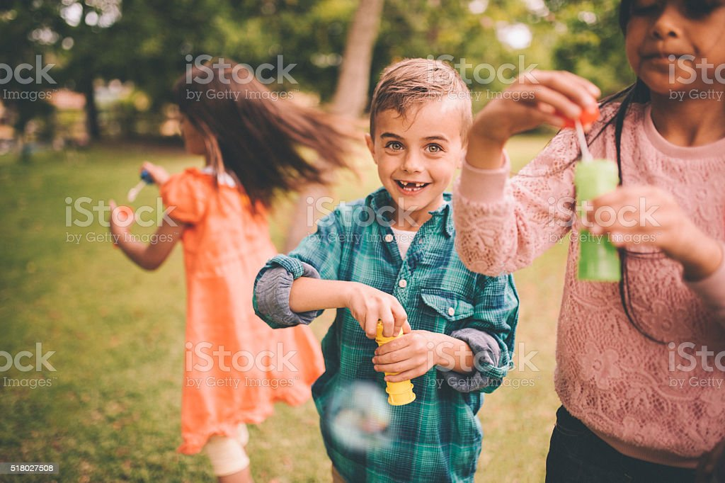 Boy with gap toothed smile playing with bubbles and friends stock photo