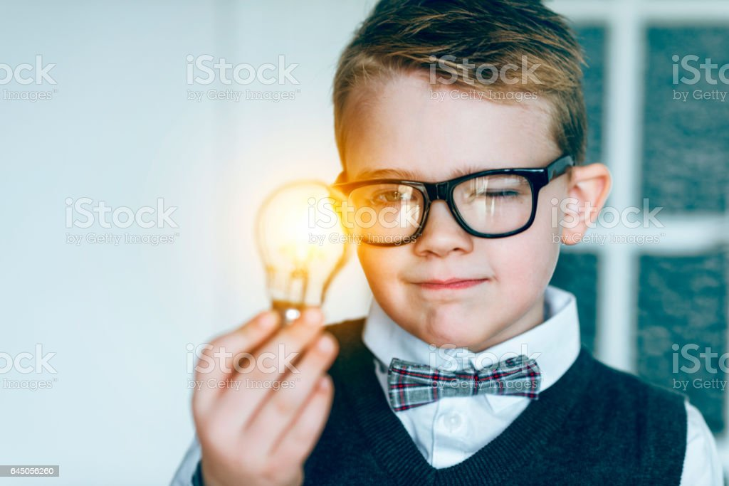 Boy with glasses and bow tie looks at glowing light bulb and gets an idea stock photo