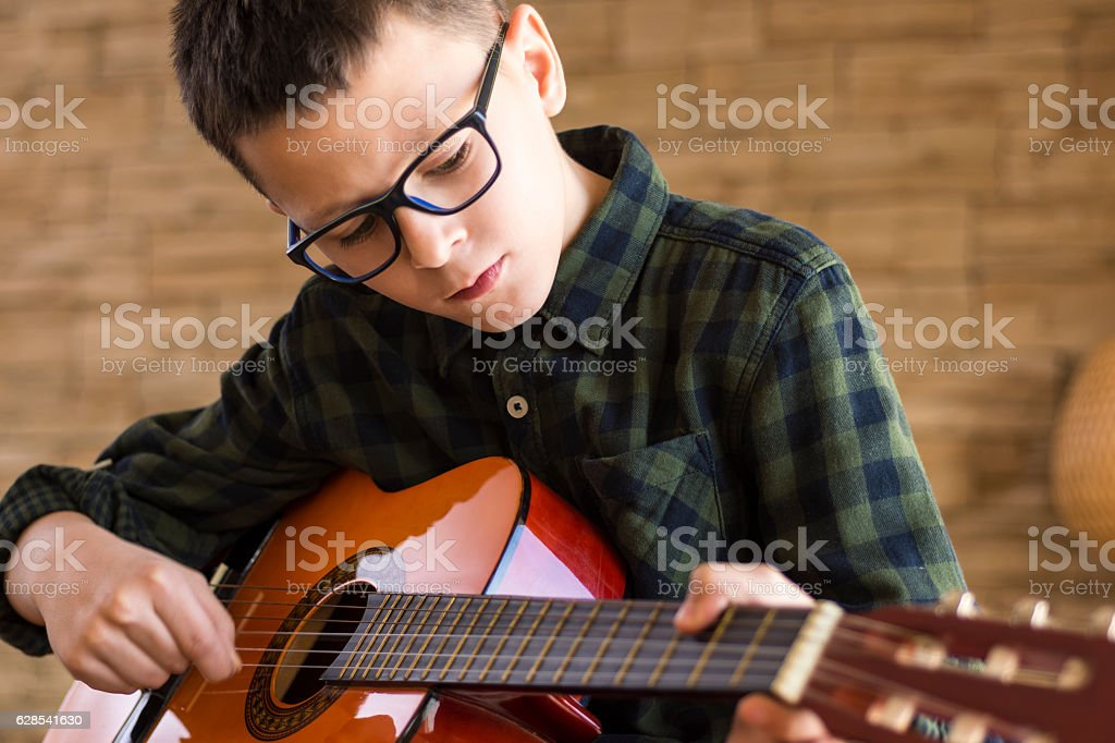 Boy With Glasses Playing Acoustic Guitar in Living Room stock photo