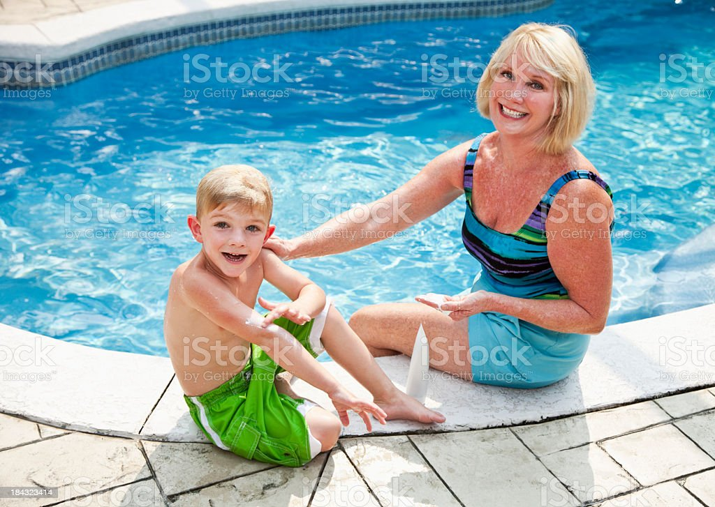 Boy with grandma putting on sunscreen stock photo