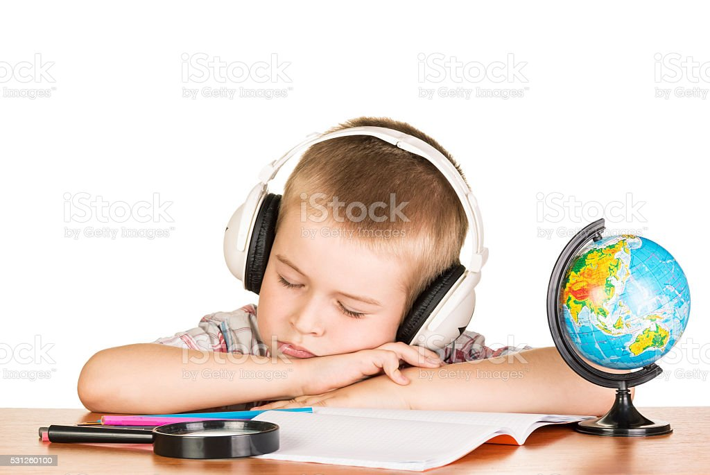 Boy with headphones, falling asleep on  notebook, isolated owhite stock photo