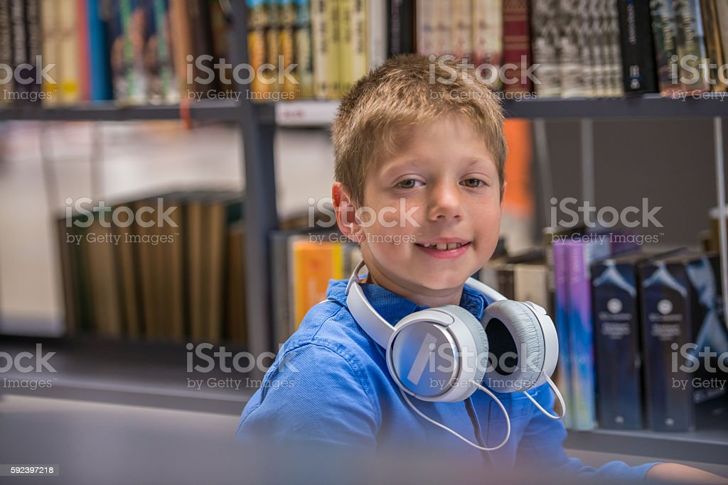 Boy With Headphones In Public Library stock photo