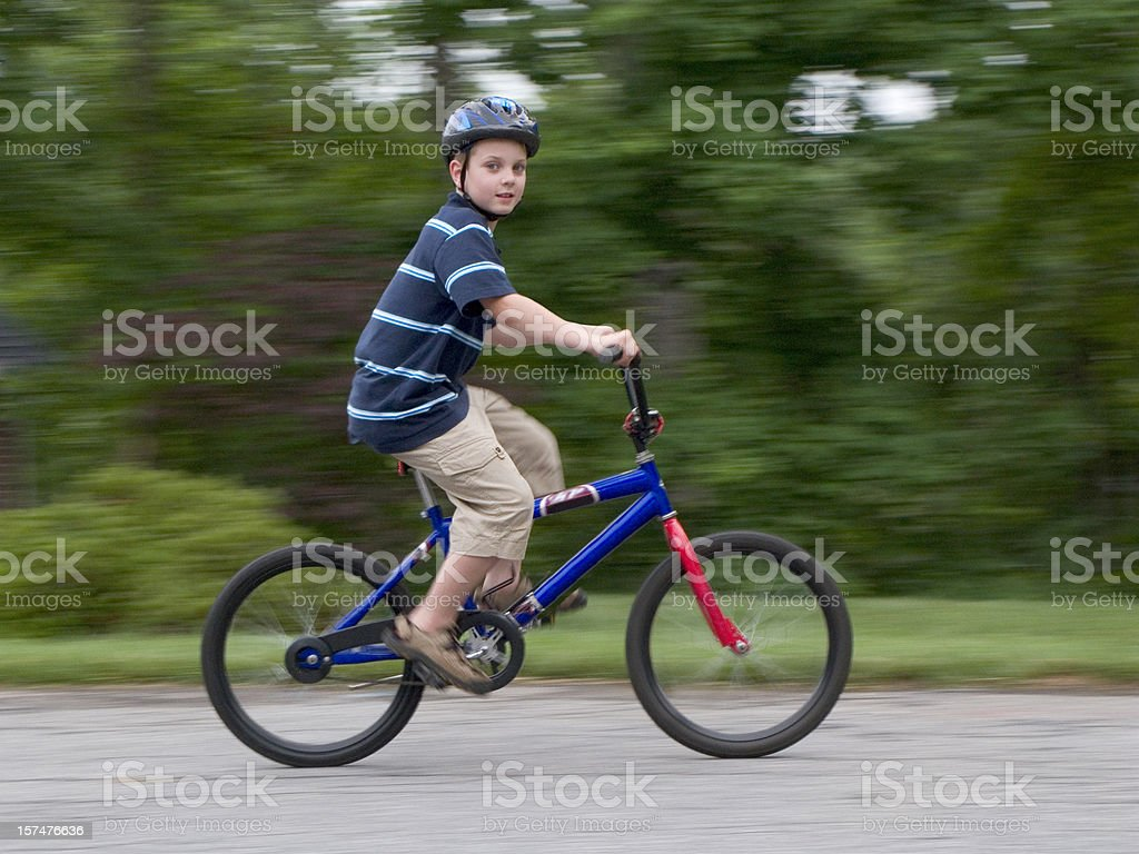 Boy With Helmet Riding Fast On Bike, Looking At Camera royalty-free stock photo