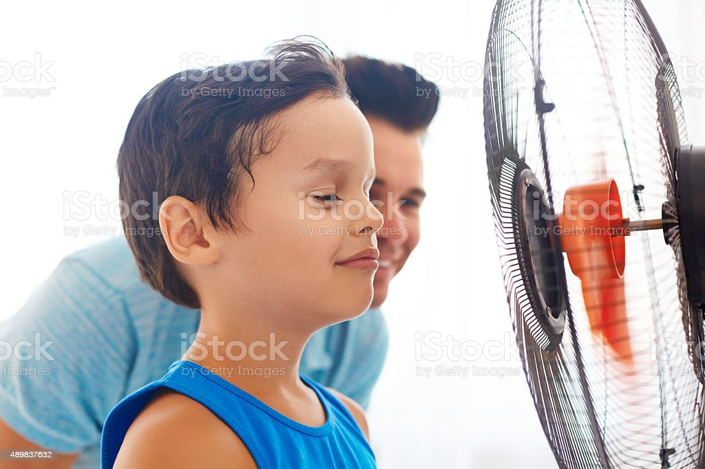 Boy with his dad cooling in front of fan. stock photo