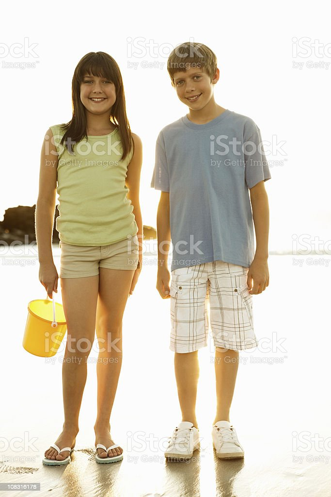 Boy with his sister holding bucket on beach stock photo