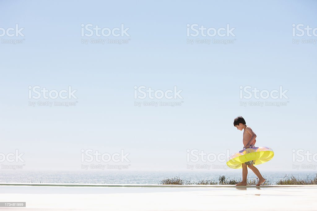Boy with inflatable ring stepping out of infinity pool royalty-free stock photo
