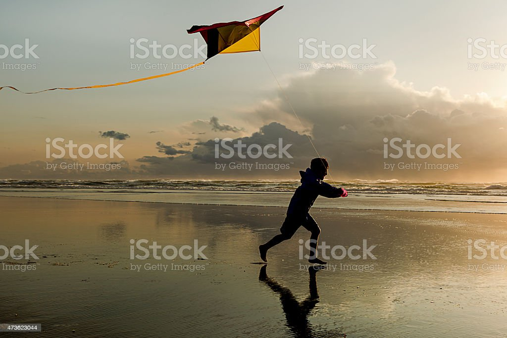 Boy with Kite at sunset. stock photo