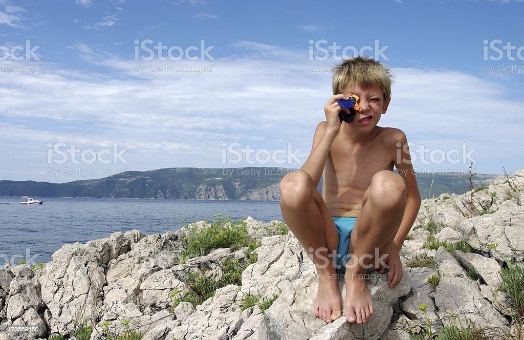 Boy with magnifying glass – beach royalty-free stock photo