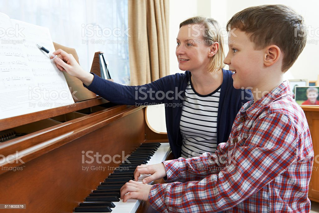 Boy With Music Teacher Having Lesson At Piano stock photo