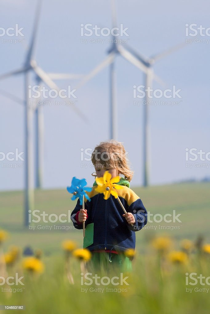 boy with pinwheel and wind farm stock photo