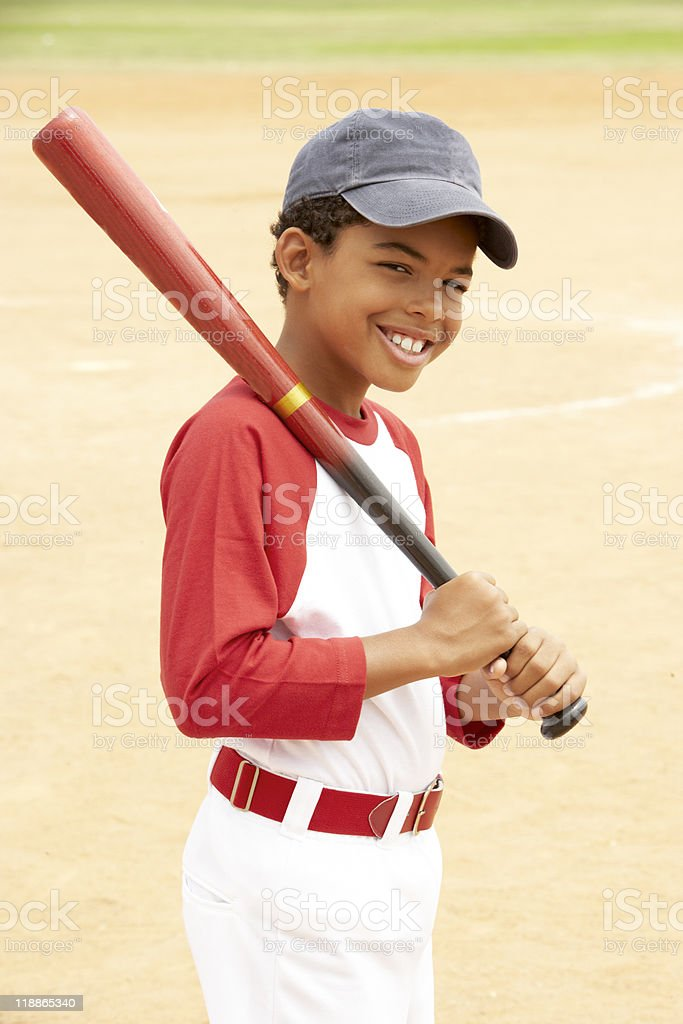 Boy with red baseball bat over shoulder on court stock photo
