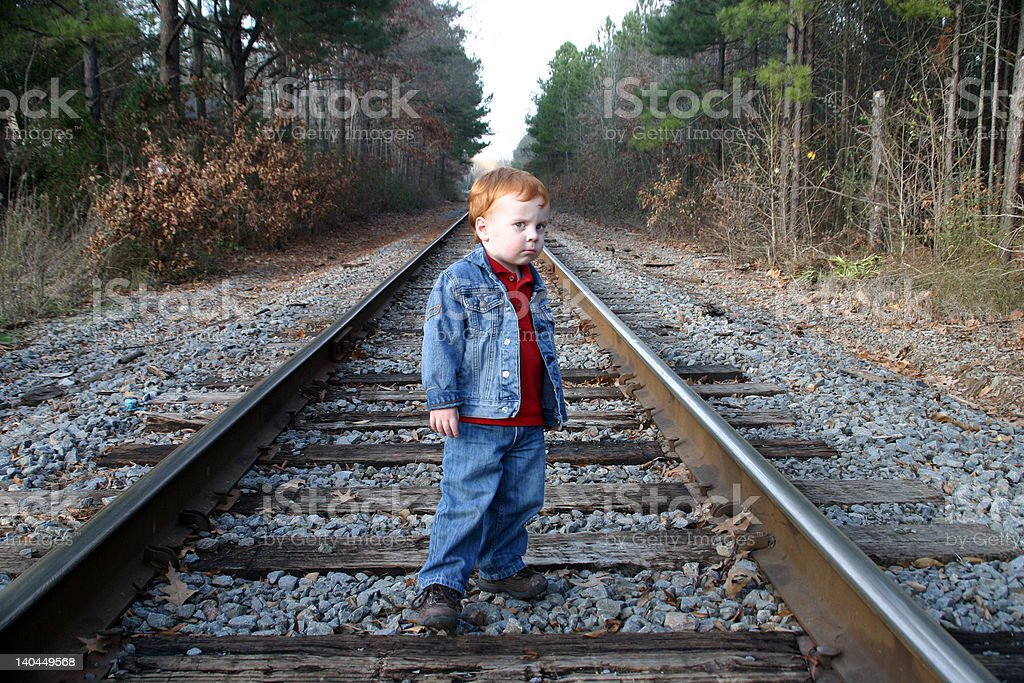 Boy with red hair on rail road tracks royalty-free stock photo