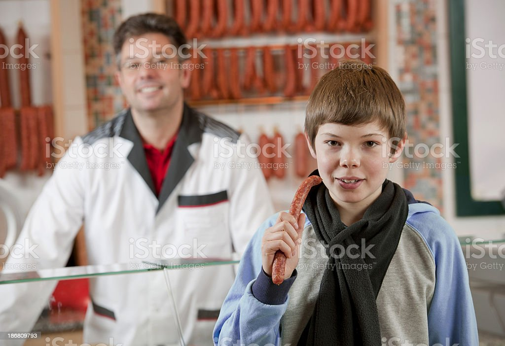 Boy with sausage in butcher's shop royalty-free stock photo