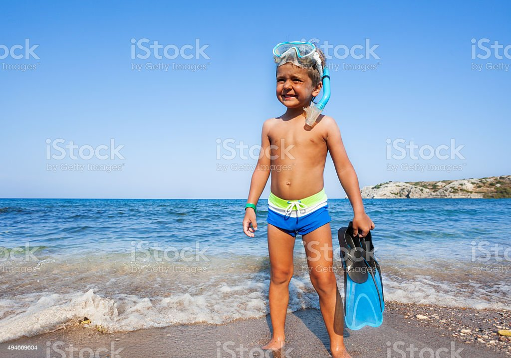 Boy with scuba mask, paddles standing on seashore stock photo