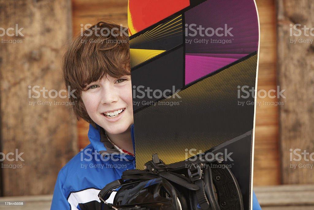 Boy With Snowboard On Ski Holiday stock photo