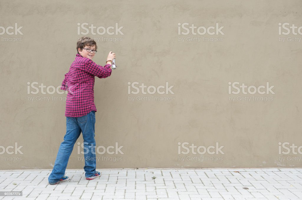 Boy with spray can and wall stock photo